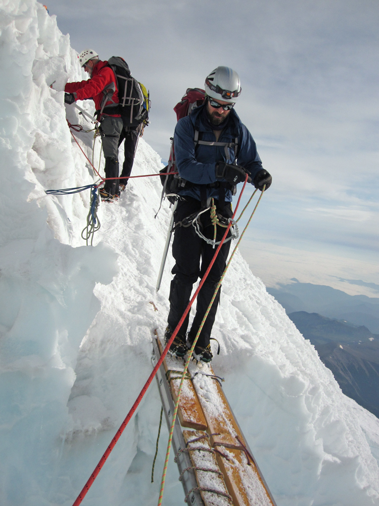 Doug makes his way across a ladder that bridges a gaping crevasse.