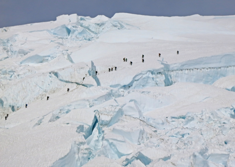 Another team makes its way across the most technical part of the route. A climber crossing a ladder over a large crevasse can be seen in the center of the photo.